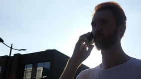 Talking on Phone in front of Sun, Outdoor Silhouette stock video