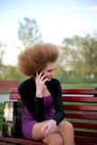 Talking on the phone the girl in the park. A pleasant phone conversation with a girl Stock Image