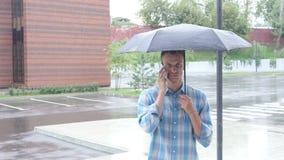 Talking on Phone, Standing Under Umbrella during Rain stock video