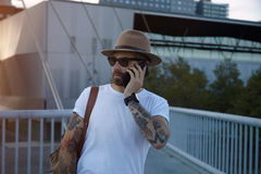 Talking on the phone at sunset. Portrait of an urban explorer at sunset talking on the phone on a bridge in a city office district Stock Image