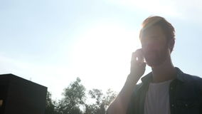 Talking on Phone during Sunset, Sun and Sky in Background stock video