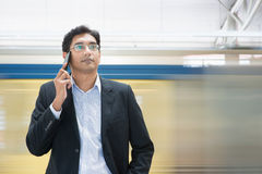 Talking on phone at train station Royalty Free Stock Photography