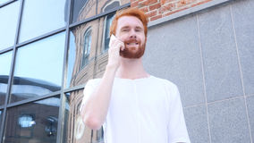 Talking on Phone, w/ Camera Moving Around Young Man, Outdoor, Red Hairs. High quality Stock Photography