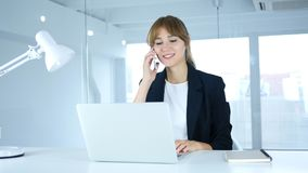 Talking on Phone, Young Female Attending Call at Work. 4k , high quality Royalty Free Stock Photos