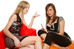 Talking playmates. Two slim sexy girls sitting on bean-bags and talking, over white background Stock Image