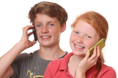 Talking. Portrait of two young teenagers talking with cell phones Royalty Free Stock Images