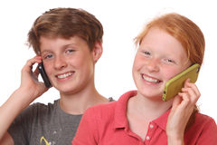 Talking. Portrait of two young teenagers talking with cell phones Royalty Free Stock Photos