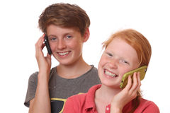 Talking. Portrait of two young teenagers talking with cell phones Stock Photo