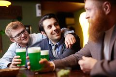 Talking in pub. Two happy guys looking at bearded men during talk by glass of beer in pub Stock Photos