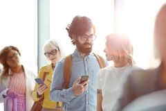 Talking in queue. Young traveler with smartphone talking to women in queue to check-in counter before departure Stock Image