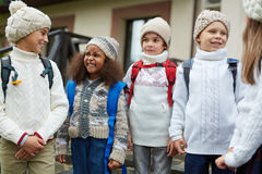 Talking school friends. Kids in knitwear talking outdoors at the end of school day Royalty Free Stock Images