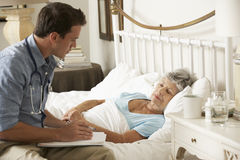 Talking With Senior Female医生患者在床上在家 免版税库存图片