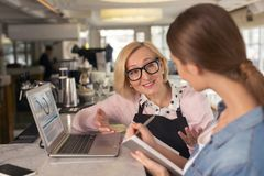 Joyful waitress discussing work with her employer. Talking about service. Cheerful blond waitress smiling and talking with her young employer Royalty Free Stock Photography