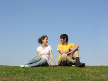 Talking sitting couple. meadow Royalty Free Stock Images