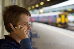 Talking at the station. A teenage boy laughing and talking on a mobile phone at a train station stock photo
