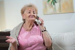 Talking on stationary telephone. Portrait of elderly woman talking on stationary telephone Stock Photography