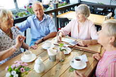 Talking by tea. Seniors gathered by table for tea and talk Royalty Free Stock Image