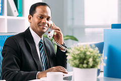 Talking on the telephone. Indian manager talking on the telephone at his workplace Royalty Free Stock Photography