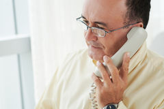 Talking on telephone. Middle-aged man in glasses talking on the telephone Stock Photos