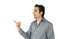 Talking To. Attractive middle eastern businessman pointing to his side like he is looking at a product or is talking to someone. Man isolated on white background Royalty Free Stock Image