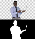 Talking to camera young african man with laptop in his hands, Alpha Channel royalty free stock photography