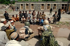 Talking to children in Azra. Interpreters from Czech Provincial Reconstruction Team in Logar Province talking to students at a school in Azra district Royalty Free Stock Images