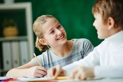 Talking to classmate. Happy schoolgirl looking at classmate while drawing stock photos