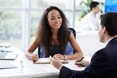Talking to her coworker. Attractive Vietnamese business lady talking to her coworker Stock Photo