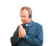 Talking to him above. Man dressed as a vicar with a headset praying Stock Photography
