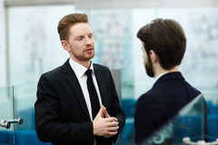 Talking to manager. Business expert or employer consulting young manager in office Stock Photography