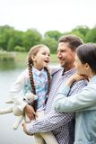 Talking to parents. Young couple and their cute daughter with teddy having fun by waterside during promenade in park stock images
