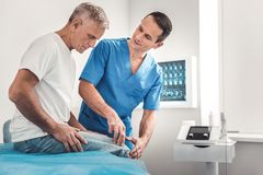 Chiropractor in blue uniform talking to his patient. Talking to patient. Chiropractor wearing blue uniform talking to his patient while working very busy all day stock photos