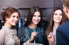 Talking to salesperson. Three girlfriends talk with salesperson stock photos