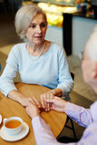 Talking to spouse. Senior female talking to her husband while holding his hands Stock Photography