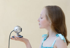 Talking to web camera. Girl is carring web camera in her hand and talking Royalty Free Stock Photography