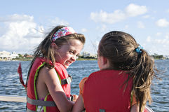 Talking by the Water. Two little girls talking while standing by the water wearing their life vests Stock Photography