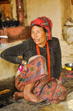 Talking woman with headcloth in Nepal. Dolpo, Nepal - circa May 2012: Photo of native woman with red headcloth dressed in black shirt and colourful skirt sitting Stock Images