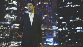 A talking young businessman dressed in a black suit at night time stock image