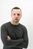 Talking young European man over white wall Stock Photo