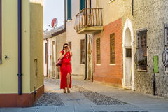 Talks on phone walking in hamlet. Sexy lady talks on flip mobile phone while walking in an old hamlet of Italian village Comacchio, known as the Little Venice Stock Images