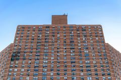 A tall apartment building complex in Harlem, with visible fire damage on the left side, New York City, NY, USA. Tall apartment building complex in Harlem, with royalty free stock photography