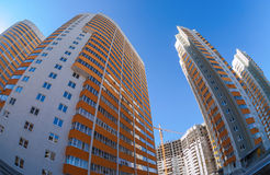 Tall apartment buildings over blue sky Stock Photos