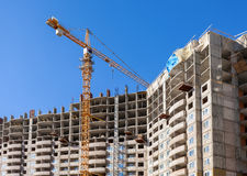 Tall apartment buildings under construction with crane against a Stock Images
