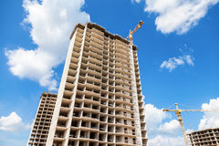Tall apartment buildings under construction with cranes against Stock Image