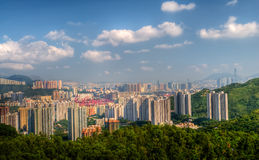 Tall apartments with green mountain under blue sky royalty free stock photo