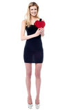 Tall attractive girl holding heart shaped gift Royalty Free Stock Photography