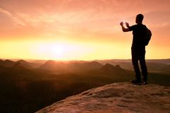 Tall backpacker with phone in hand. Spring daybreak in mountains. stock image