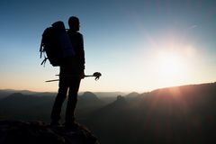 Tall backpacker with poles in hand. Sunny hike day in rocky mountains. Hiker with big backpack stand on rocky view point above mis. Tall backpacker with poles in Royalty Free Stock Photography
