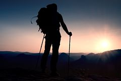 Tall backpacker with poles in hand. Sunny hike day in rocky mountains. Hiker with big backpack stand on rocky view point above mis Royalty Free Stock Photo