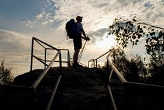Tall backpacker with poles in hand. Sunny spring daybreak in rocky mountains. Hiker with big backpack, baseball cap, pants and whi Royalty Free Stock Images